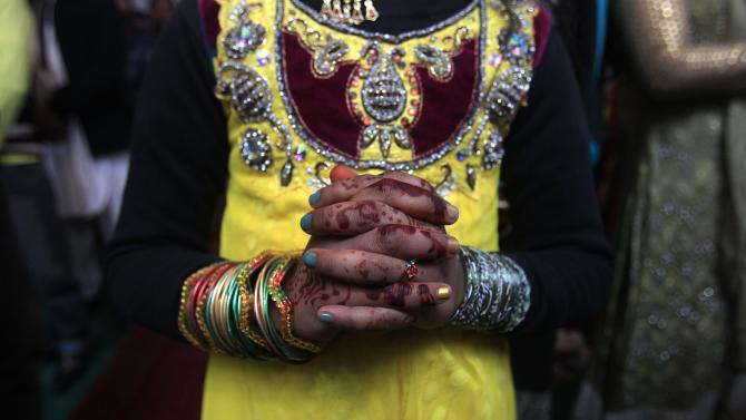 Girl with henna-dyed hands, attend a mass on Christmas day at the St John's Cathedral Church, in Peshawar