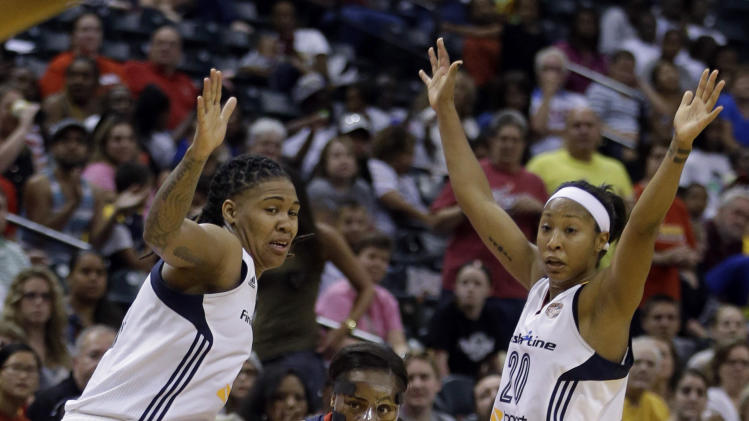 Washington Mystics' Ivory Latta, center, makes a pass against Indiana Fever's Erlana Larkins, left, and Briann January during the second half of Game 1 of a WNBA basketball Eastern Conference semifinal Thursday, Aug. 21, 2014, in Indianapolis. Indiana defeated Washington 78-73. (AP Photo/Darron Cummings)