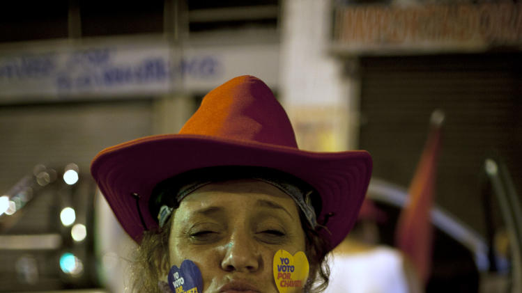 A supporter of Venezuela's President Hugo Chavez celebrates in downtown Caracas, Venezuela, Sunday, Oct. 7, 2012.  Chavez won re-election and a new endorsement of his socialist project Sunday, surviving his closest race yet after a bitter campaign against opposition candidate Henrique Capriles.(AP Photo/Ariana Cubillos)