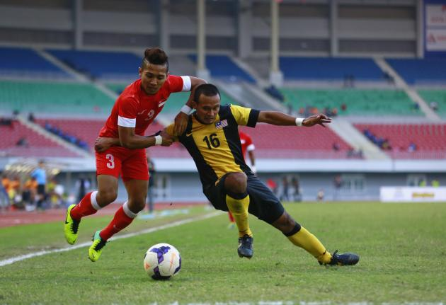 Mohamad Sahil Suhaimi of Singapore and Mohd Azmi Mohd Zubir of Malaysia fight for ball during soccer men's bronze medal match at 27th SEA Games in Naypyitaw