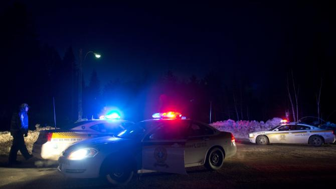 Police vehicles block a road just outside the town of Chertsey, Quebec, Sunday, March 17, 2013, during a search for escaped prisoners. A dramatic daylight jailbreak involving two Quebec inmates climbing a rope into a hovering helicopter swiftly escalated into a large police operation Sunday night in which at least one escapee was tracked down hours after he fled. (AP Photo/The Canadian Press, Graham Hughes)