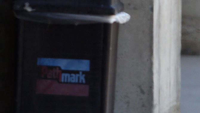 An evidence marker stands next to broken glass in front of a Pathmark grocery store where three people died in an early morning shooting in Old Bridge, N.J., Friday, Aug. 31, 2012.  Officials say a supermarket employee killed two people at the store early Friday and then fatally shot himself. Authorities say he opened fire on employees he saw when he walked into the Pathmark store. The store's front windows were shattered by gunfire.  The motive is being investigated.(AP Photo/Julio Cortez)