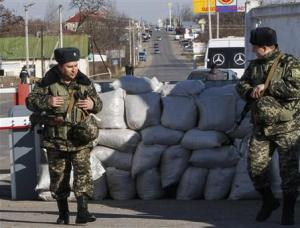 Ukrainian border guards stand at a checkpoint at the …