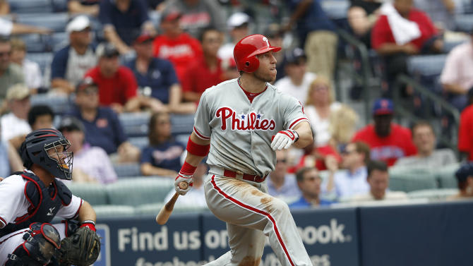 Philadelphia Phillies first baseman Laynce Nix (19) follows through with a solo home run as Atlanta Braves catcher David Ross (8) looks on in the seventh inning of a baseball game in Atlanta, on Thursday, May 3, 2012. (AP Photo/John Bazemore)