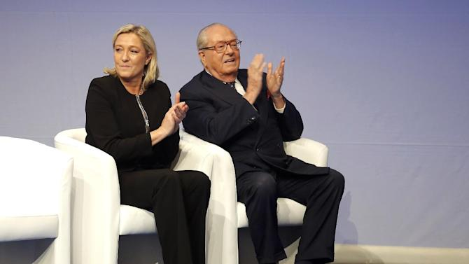 FILE - In this Saturday Nov. 29, 2014 file photo, French far-right Front National leader Marine Le Pen and her father Jean-Marie Le Pen applaud during the 15th congress of the party, in Lyon, central France. A pact of sorts may end the bloodletting between Le Pen and her 86-year-old father, Jean-Marie Le Pen, a party founder whose latest anti-Semitic remarks have tripped up the efforts of his daughter to give the National Front a new look. She announced on national television she will oppose his candidacy in December regional elections. (AP Photo/Laurent Cipriani, File)