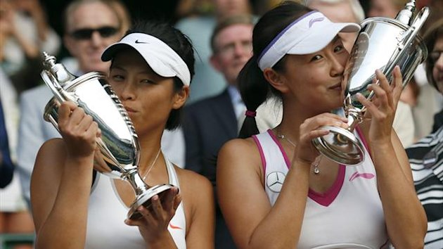 Peng Shuai of China (R) and Hsieh Su-Wei of Taiwan kiss their winners trophies after defeating Ashleigh Barty of Australia and Casey Dellacqua of Australia in their women's doubles final tennis (Reuters)