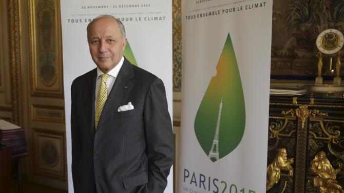 French Foreign Affairs Minister Fabius poses in front of the Paris 2015 climate change conference logo in his office in Paris
