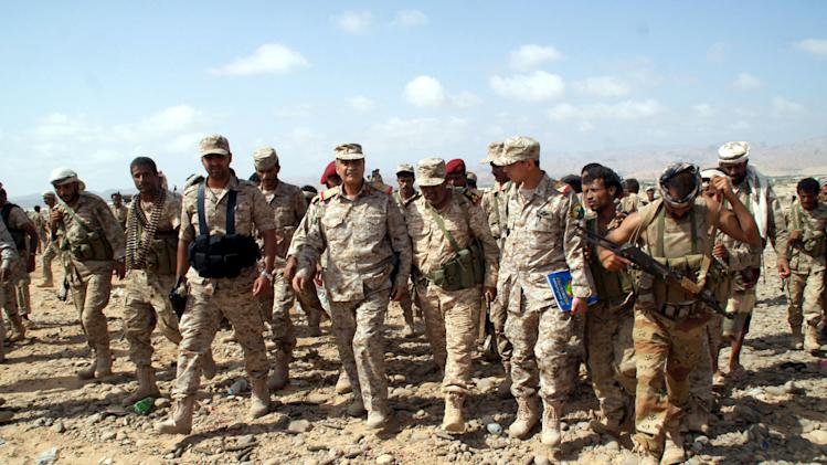 In this photo provided by Yemen's Defense Ministry, Yemeni Defense Minister Mohammad Nasser Ahmad, center left, inspects the troops at areas seized from al-Qaida in the southeastern province of Shabwa, Yemen, Thursday, May 8, 2014. Yemeni armed forces on Thursday swept al-Qaida fighters out of a district in the country's south, one of the main goals of the major offensive waged by the military the past two weeks, the Defense Ministry said, amid fears of retaliatory attacks which officials say prompted the closure of the US embassy in the capital as a precaution. (AP Photo/Yemen's Defense Ministry)