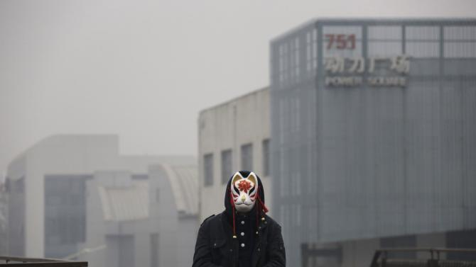 A performer wearing a mask waits to take part in a short film production on a hazy day at Beijing's 798 art zone