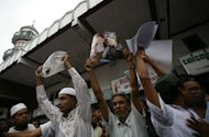 Myanmar Muslims hold up pictures of recent violence in Rakhine state during a gathering in Yangon on June 5. Myanmar&#39;s reformist government has launched an official probe into a flare-up of sectarian violence in the west of the country, state media said, pledging to punish those responsible