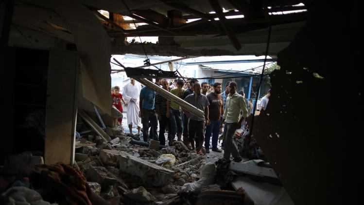 Palestinians look at a damaged classroom at a United Nation-run school sheltering Palestinians displaced by an Israeli ground offensive, that witnesses said was hit by Israeli shelling, in Jebalya refugee camp in the northern Gaza Strip