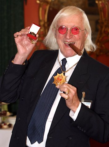 FILE - This is a March 25, 2008 file photo of Sir Jimmy Savile, who for decades was a fixture on British television. A year after he died, aged 84 and honored as Sir Jimmy, several women have come forward to claim he was also a sexual predator and serial abuser of underage girls. The child abuse scandal that has enveloped the BBC, one of Britain's most respected news organizations, is now hitting one of America's, as the incoming president of The New York Times is on the defensive about his final days as head of the BBC. Mark Thompson was in charge of the BBC in late 2011 when the broadcaster shelved what would have been a bombshell investigation alleging that the late Savile was a serial sex offender. (AP Photo/ Lewis Whyld/PA, File)