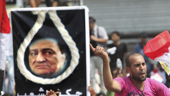 "An Egyptian protester shouts slogans in front of a poster showing ousted President Hosni Mubarak on a noose during a protest at Tahrir Square, the focal point of the Egyptian uprising, in Cairo, Egypt Friday, Sept.9, 2011. Thousands protested demanding a clear road map to democracy and an end to military trials for civilians, calling the Friday protest  ""Correcting the Path"" . Arabic reads "" people's verdict"".  (AP Photo/Amr Nabil)"