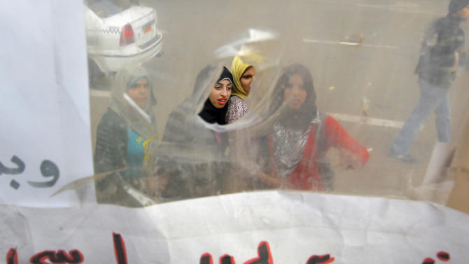 """Egyptians read slogans on a poster displayed in a temporary exhibit of revolutionary paraphernalia in Tahrir Square in Cairo, Sunday, Dec. 30, 2012. Arabic reads, """" Morsi, you don't have any legality."""" (AP Photo/Amr Nabil)"""