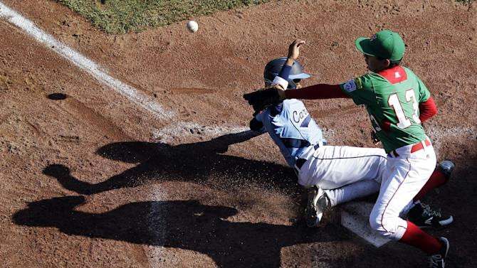 Willemstad, Curacao's Richelon Juliana, left, scores past Nuevo Laredo, Mexico's Andres Carrillo on a wild pitch in the third inning of a baseball game at the Little League World Series, Tuesday, Aug. 21, 2012, in South Williamsport, Pa. Mexico won 6-2. (AP Photo/Matt Slocum)