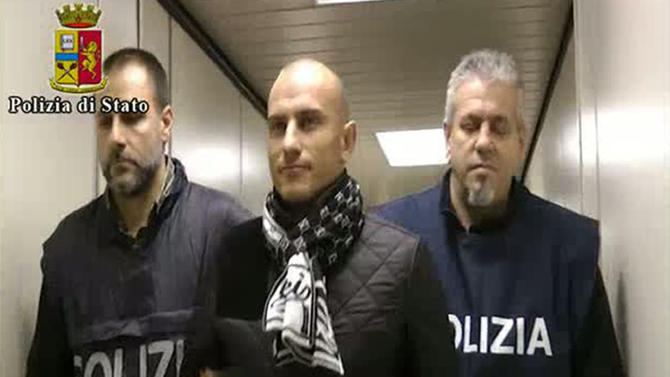 In this frame grab from a video released by the Italian Police, Serbian footballer Almir Gegic, who has been wanted since June 2011 for alleged involvement in a widespread match-fixing case, is escorted by police after he arrived at the Malpensa airport in the outskirts of Milan, Italy, Monday evening, Nov. 26, 2012. After more than a year on the run, Gegic turned himself in and was brought to a jail in Cremona, where prosecutor Roberto Di Martino's match-fixing inquiry is based. More than 50 people have been arrested so far and more than 100 are under investigation. (AP Photo/Italian Police, HO)