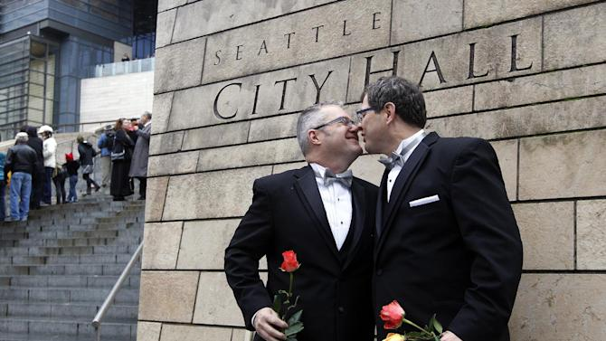 FOR USE AS DESIRED, YEAR END PHOTOS - FILE - Terry Gilbert, left, kisses his husband Paul Beppler after wedding at Seattle City Hall, becoming among the first gay couples to legally wed in the state, Sunday, Dec. 9, 2012, in Seattle. Gov. Chris Gregoire signed a voter-approved law legalizing gay marriage Dec. 5 and weddings for gay and lesbian couples began in Washington on Sunday, following the three-day waiting period after marriage licenses were issued earlier in the week. (AP Photo/Elaine Thompson)