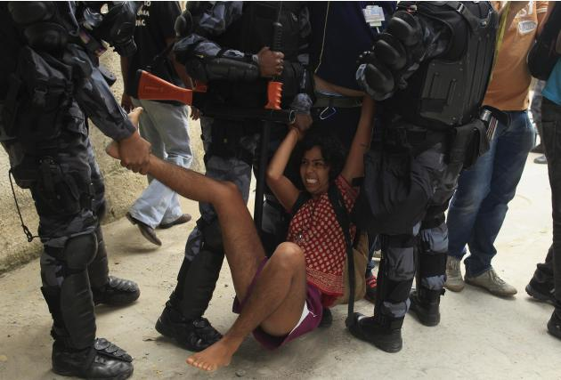 A supporter of a native Indian community is dragged by police officers outside the Indian museum in Rio de Janeiro
