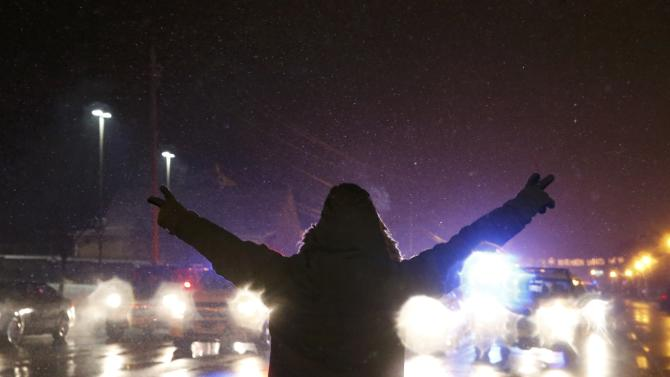 A protester walks in the street with his hands up as National Guard vehicles drive by after the grand jury verdict in the Michael Brown shooting in Ferguson, Missouri