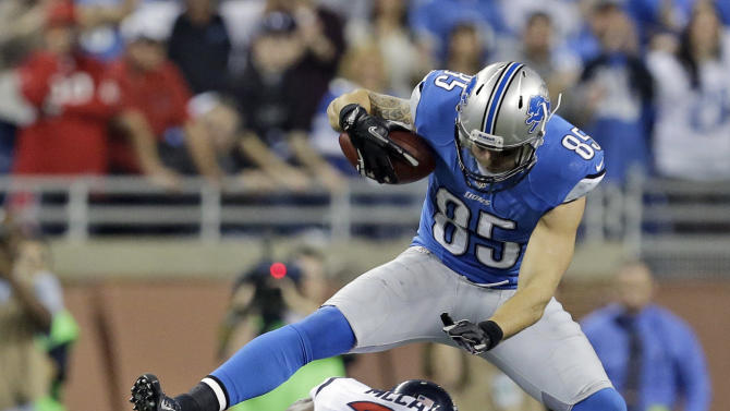 Detroit Lions tight end Tony Scheffler (85) jumps over Houston Texans defensive back Brice McCain (21) during overtime of an NFL football game at Ford Field in Detroit, Thursday, Nov. 22, 2012. (AP Photo/Paul Sancya)