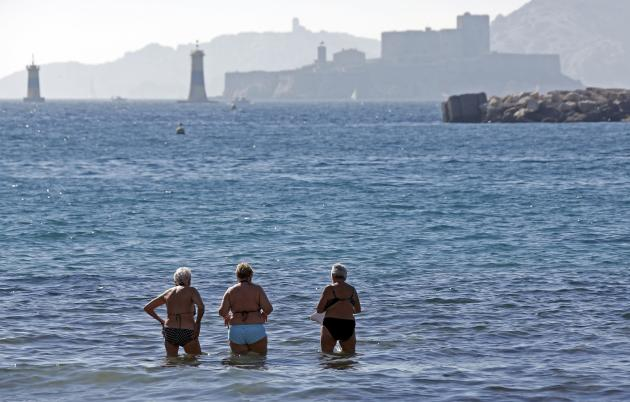 People stand in the Mediterranean Sea during a warm and sunny winter day in Marseille