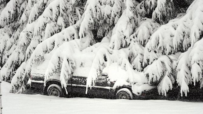 A lone parked car is draped  with snow covered branches south of Morgantown, W.Va. from a snowfall on Tuesday, Oct. 30, 2012. West Virginia's death toll climbed to at least six and hundreds of thousands remained without power Wednesday, Oct. 31, from the wet, heavy snow that superstorm Sandy dumped on the mountains, snapping trees, pulling down power lines and collapsing homes. (AP Photo/The Dominion-Post, Ron Rittenhouse)