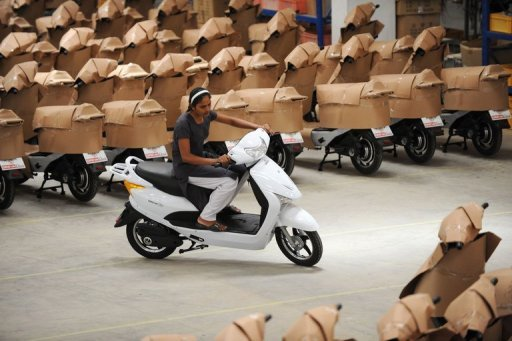 <p>An Indian woman worker test drives an electric scooter at a factory near Samakhiali. India's economy accelerated slightly in the April-June quarter, growing by 5.5 percent year-on-year and beating market forecasts, official data showed Friday.</p>