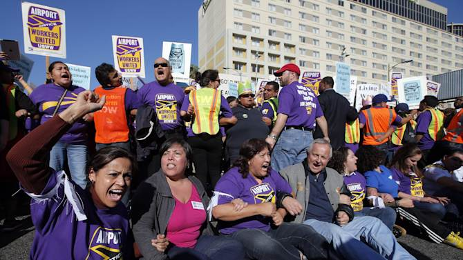 Union workers at Los Angeles International Airport chant their slogans during a protest in Los Angeles, Wednesday, Nov. 21, 2012. Hundreds of union members marched Wednesday near the entrance to Los Angeles International Airport, where Thanksgiving travelers were warned to arrive early in case of traffic snarls. (AP Photo/Jae C. Hong)