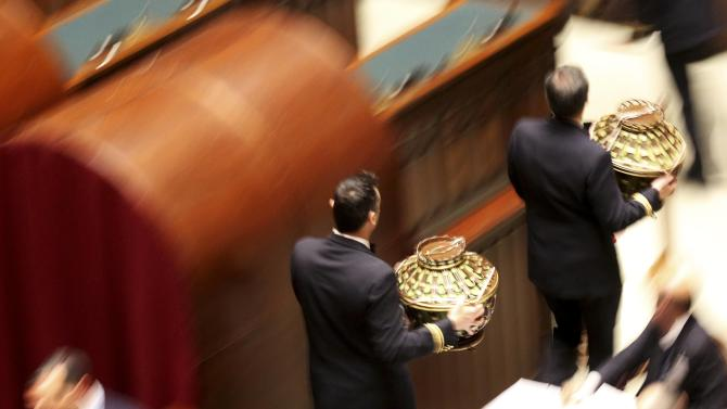 Assistants carry the ballot boxes at the end of the voting session at the Chambers of Deputies in Rome