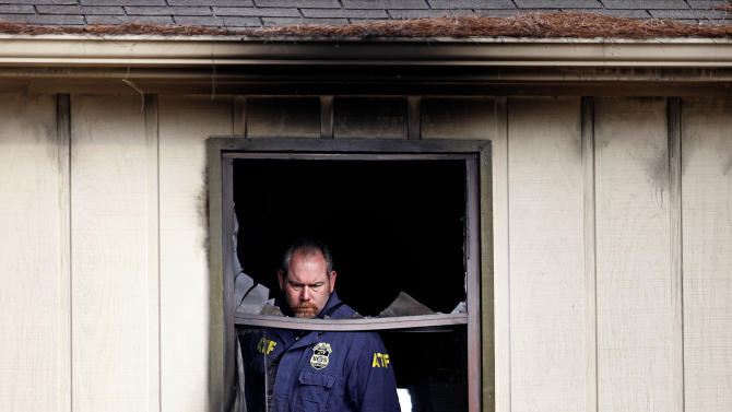 An Alcohol, Tobacco and Firearms agent inspects the second floor scene of a house fire that killed four children, including an infant, Wednesday, Jan. 9, 2013, in Conyers, Ga. The fire burned late Tuesday night at a duplex in Conyers, east of Atlanta. Another child, who is 6, was thrown by his mother from a second-floor window, said Glenn Allen, a spokesman for Georgia's fire commissioner. The child injured his shoulder in the fall but survived. The mother was taken to Grady Memorial Hospital in Atlanta with second- and third-degree burns, Allen said. (AP Photo/David Goldman)