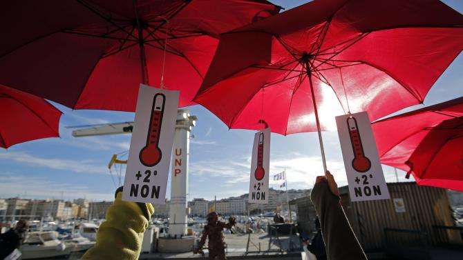 Environmental activists hold red umbrellas as they take part in a symbolic human chain gathering after the cancellation of a planned climate march following shootings in the French capital ahead of the World Climate Change Conference 2015 in Marseille