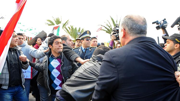 Pro Syrian demonstrators scuffle with police as they are protesting outside the Cartago Hotel where the  Conference on Syria is held in Tunis, Tunisia, Friday Feb. 24, 2012.The birthplace of the Arab Spring hosts a landmark conference on Syria by high-level U.S., European, Turkish and Arab League officials. The protesters, waving Syrian and Tunisian flags, tussled with police and carried signs criticizing Clinton and President Barack Obama.(AP Photo/Hassene Dridi)