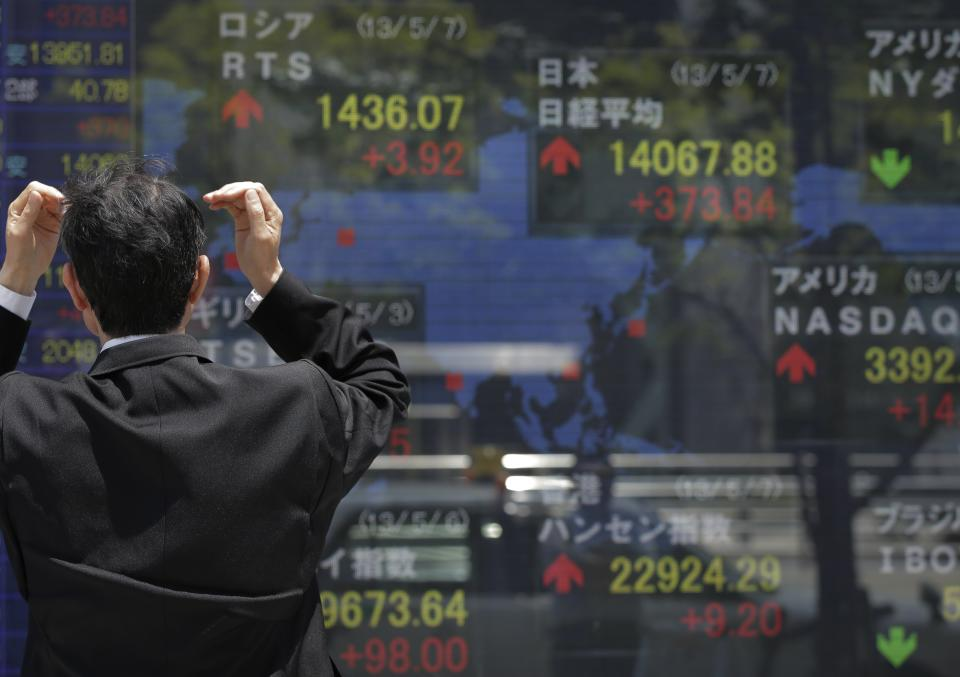 A man looks at the electronic stock board of a securities firm in Tokyo, Tuesday, May 7, 2013. Japan's benchmark stock index, reopening after a long weekend holiday, surged Tuesday in the wake of a U.S. jobs report issued late last week that handily beat expectations. (AP Photo/Itsuo Inouye)