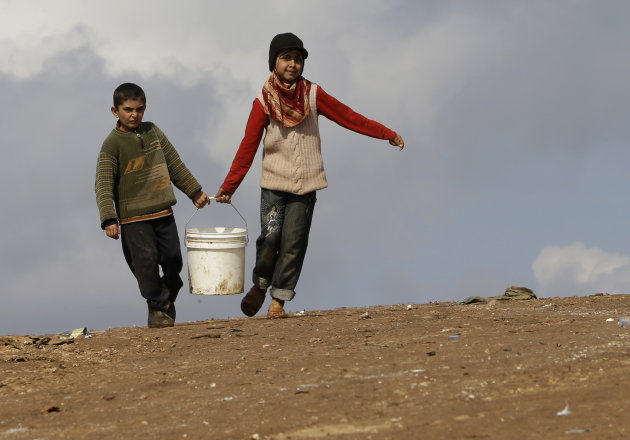 In this Tuesday, Feb. 19, 2013 photo, Syrian refugees carry a bucket of water as they walk at Atmeh refugee camp, in the northern Syrian province of Idlib, Syria. This rebel-controlled camp only yards