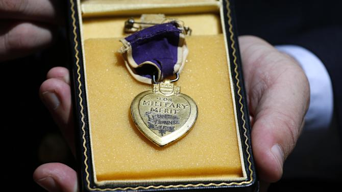 Purple Hearts Reunited founder Capt. Zachariah Fike, who was wounded in Afghanistan while serving with the Vermont Army National Guard, displays a Purple Heart from Pearl Harbor which has yet to be reunited with its owner or relatives, during the National Order of the Purple Heart National Convention in Denver, Thursday Aug. 7, 2014. Purple Hearts Reunited receives lost Purple Hearts and works to reunite the medals with their original owners. (AP Photo/Brennan Linsley)