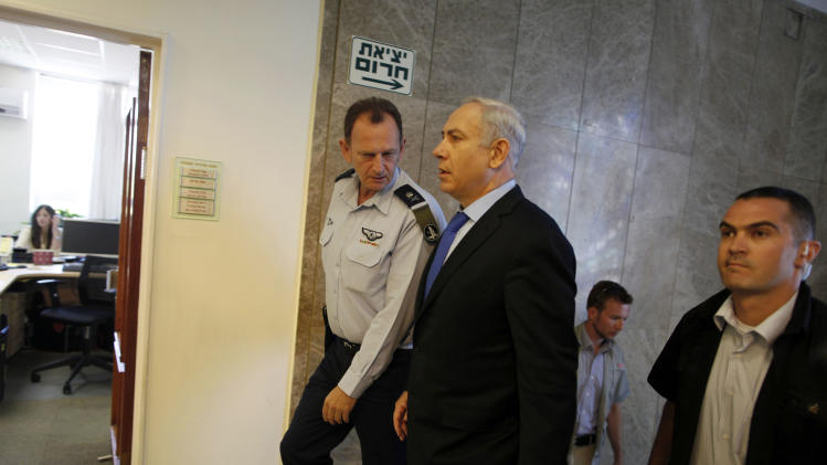 Israeli Prime Minister Benjamin Netanyahu, center, arrives for a weekly cabinet meeting at his Jerusalem office, Sunday, June 3, 2012. An Israeli official said on Saturday Netanyahu is mulling whether to demolish or relocate a West Bank outpost ahead of a court deadline for its removal. (AP Photo/Lior Mizrahi, Pool)