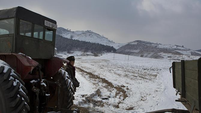 A North Korean man stands next to a tractor and wagon on the edge of a snow covered field near the village of Ryongsan-ri, south of Pyongyang, North Korea on Friday, Feb. 22, 2013. (AP Photo/David Guttenfelder)