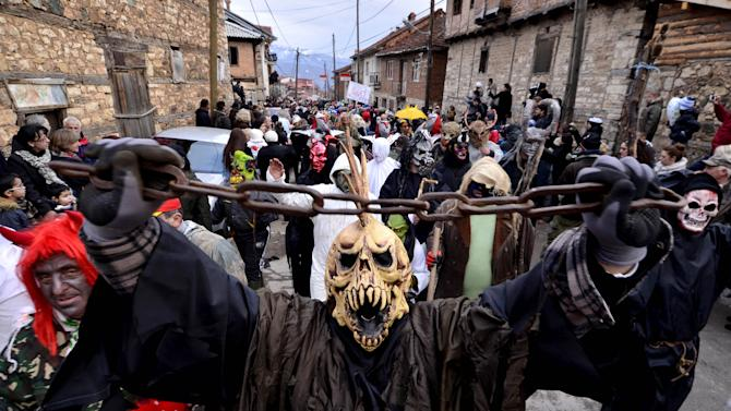 In this picture taken Sunday, Jan. 13, 2013, masked villagers parade during the carnival in Macedonia's southwestern village of Vevcani.  Said to date from pagan times 1,400 years ago, the Vevcani carnival, with its colorful floats and masked revelers, has grown in popularity over the last decade and attracts thousands of visitors for the celebrations on St. Vasilij Day to welcome in the New Year according to the Julian calendar. (AP Photo/Boris Grdanoski)