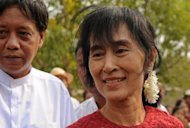 Myanmar opposition leader Aung San Suu Kyi smiles as she leaves after visiting a polling station in the constituency where she stands as a candidate in Kawhmu. Myanmar's opposition claimed a historic victory for Suu Kyi in her bid for a seat in parliament, sparking scenes of jubilation among crowds of supporters