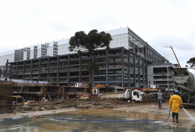 Workers are pictured on the job outside the Arena da Baixada soccer stadium as it is being built to host matches of the 2014 World Cup in Curitiba