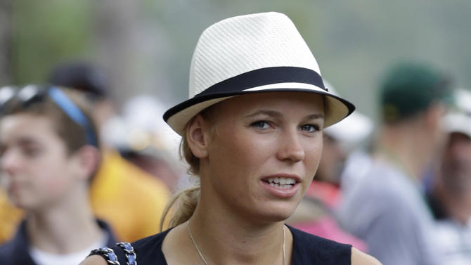 Tennis player Caroline Wozniacki follows Rory McIlroy, of Northern Ireland, during his second round of the Masters golf tournament Friday, April 12, 2013, in Augusta, Ga. (AP Photo/Darron Cummings)