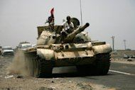Traffic moves slowly behind a Yemeni tank on a main road near the southern city of Zinjibar. At least 16 people have been killed in clashes in Yemen&#39;s southern province of Abyan where Al-Qaeda and the army are battling for control of the restive territory