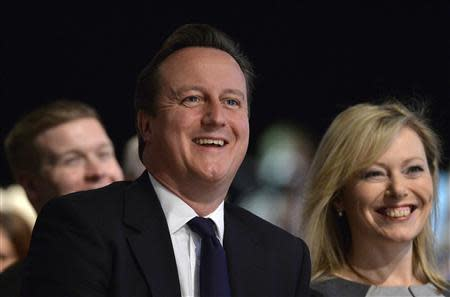 Britain's Prime Minister Cameron and Ffion Hague listen to Foreign Secretary Hague deliver his keynote speech first day of the Conservative Party annual conference in Manchester northern England