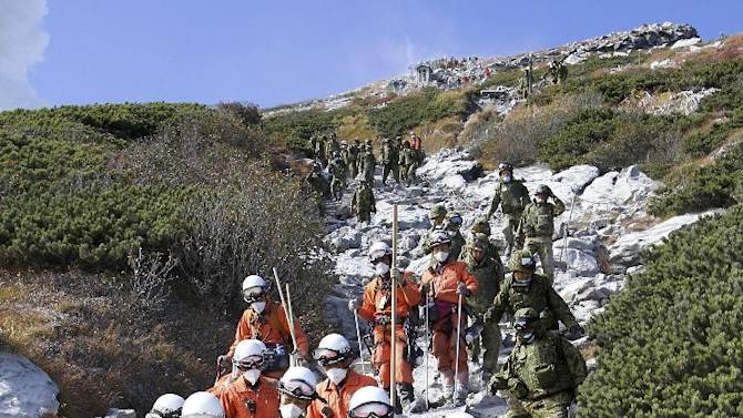 In this Sunday, Sept. 28, 2014 photo released by Tokyo Fire Department, firefighters carry an injured by Saturday's initial eruption from the summit of Mount Ontake in central Japan. A dozen more bodies were found Wednesday, Oct. 1 near the ash-covered summit of the Japanese volcano as searches resumed amid concern of toxic gasses and another eruption. (AP Photo/Tokyo Fire Department) EDITORIAL USE ONLY