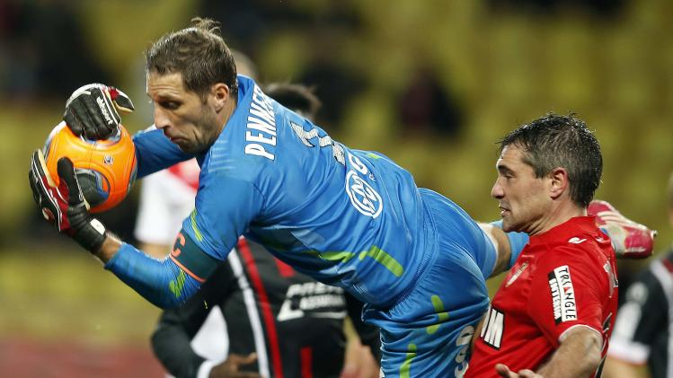 Valenciennes goalkeeper Nicolas Penneteau challenges AS Monaco's Jeremy Toulalan during their French Ligue 1 soccer match at Louis II stadium
