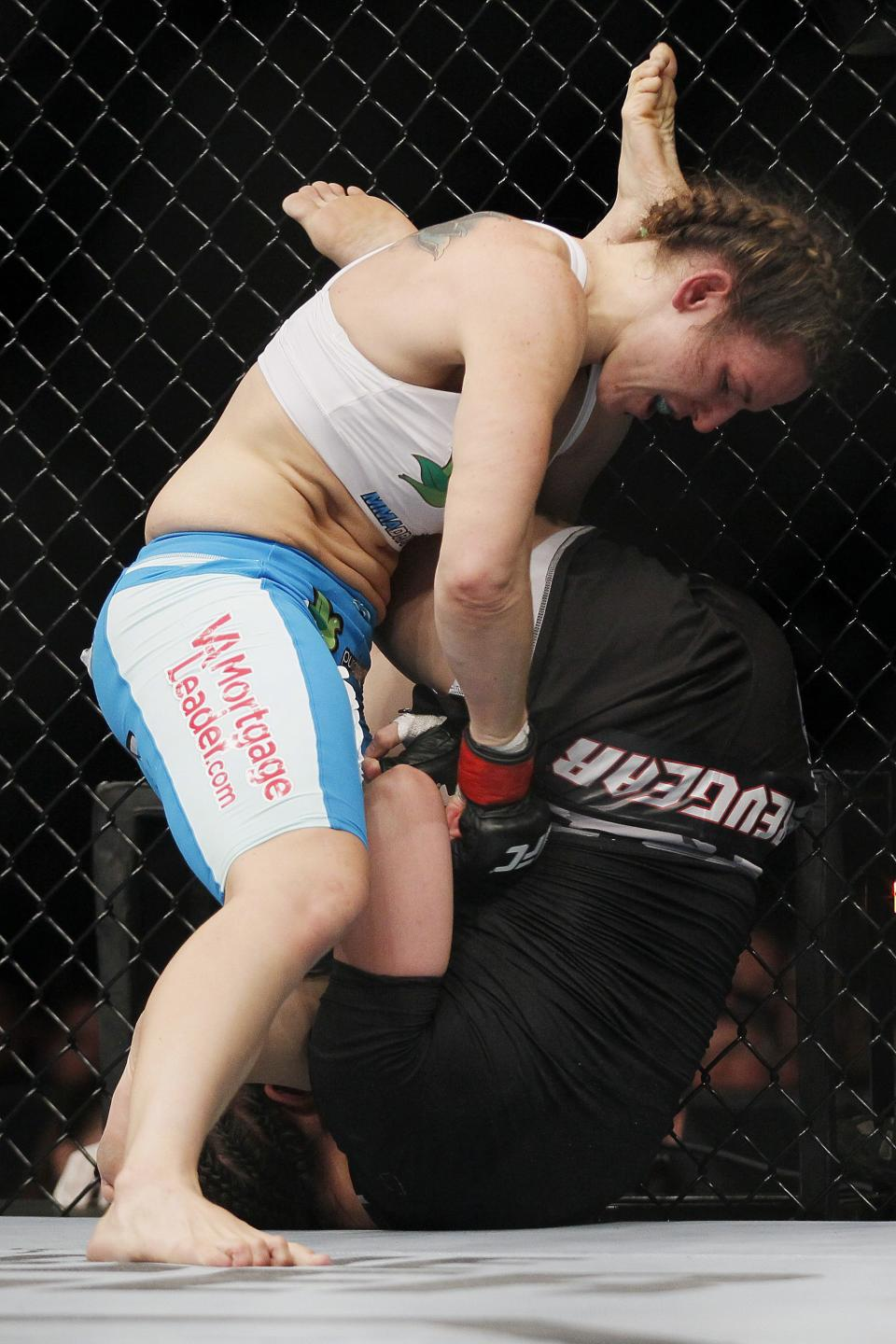 Alex Davis drives down hard on Rosi Sexton during their women's bantamweight bout at UFC 161 in Winnipeg on Saturday June 15, 2013. (AP Photo/The Canadian Press, John Woods)