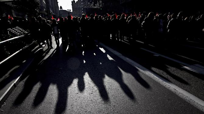 Demonstrators are seen backlighted as they march through Gran Via street during a general strike in Madrid, Spain, Wednesday, Nov. 14, 2012. Spain's General Workers' Union said the nationwide stoppage, the second this year, was being observed by nearly all workers in the automobile, energy, shipbuilding and constructions industries. (AP Photo/Daniel Ochoa de Olza)