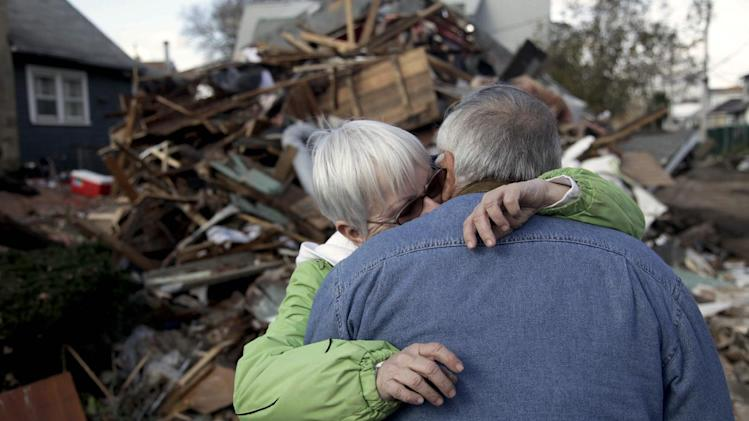 Sheila and Dominic Traina hug in front of their home which was demolished during Superstorm Sandy in the Staten Island borough of New York, Friday, Nov. 2, 2012.  A Superstorm Sandy relief fund is being created just for residents of the hard-hit New York City borough. Former Mayor Rudolph Giuliani and Borough President James Molinaro say the fund will help residents displaced from their homes. (AP Photo/Seth Wenig)