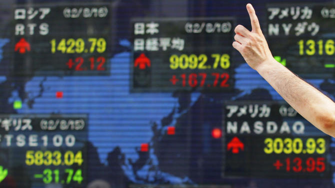 A man gestures in front of a securities firm's electronic stock board in Tokyo Thursday, Aug. 16, 2012. Japan's Nikkei 225 index rose 1.88 percent to 9,092.76 Thursday as Asian stock markets were mostly higher after comments from Chinese Premier Wen Jiabao added to hopes for more action to spur the world's No. 2 economy. (AP Photo/Shizuo Kambayashi)