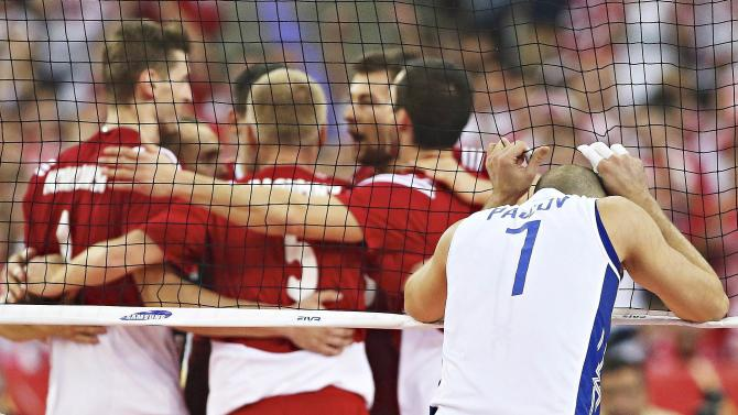 Russia's Pavlov reacts as Poland's players celebrate a point during their third round match of the FIVB Volleyball Men's World Championship Poland 2014 at the Atlas Arena in Lodz